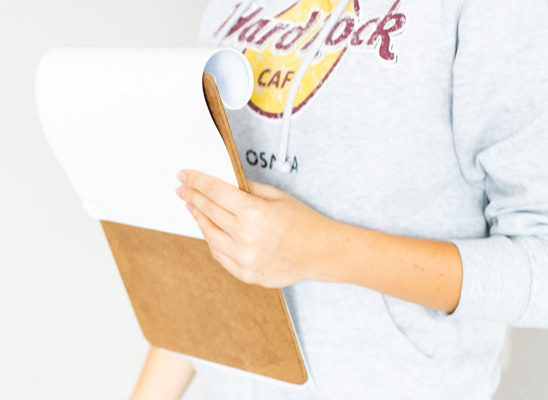 Photo of woman holding clipboard